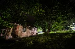 Mountain night landscape of building at forest in foggy night with moon. Green meadow, big trees and abandoned house at night. Nig. Mountain night landscape of stock images