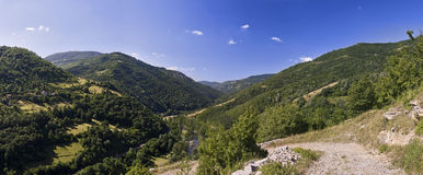 Mountain panorama. Summer day mountain panorama with forests Stock Images