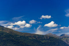 Mountain panorama and bright blue sky. A view of the mountains surrounding Lake Como, Italy Royalty Free Stock Images