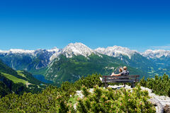 Mountain panorama. Couple sitting on a bench in front of the alps enjoying the mountain panorama Stock Photo