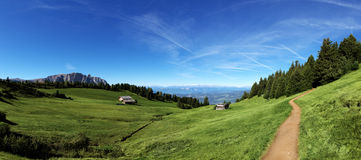 Mountain panorama. Italian mountain panorama in Tyrol with chalet and green pastures on a sunny day Royalty Free Stock Images