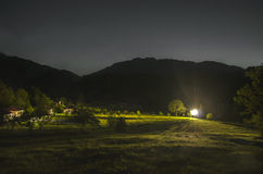 Mountain panorama night landscape. valley with grass on hillside of mountain range. Green meadow with houses and strong light. Cau. Casus, Lahic, Azerbaijan Royalty Free Stock Image