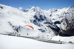 Mountain panorama with paraglider. Alpen trip mountainside vista panorama of plateau. Bright blue heaven above high crag. Wintertime scenic top view. Beautiful Stock Photo