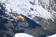 Mountain panorama with paraglider. Alpen trip mountainside vista panorama of rock summit plateau scene. Bright blue heaven above tall crag. Wintertime sunlight Royalty Free Stock Images