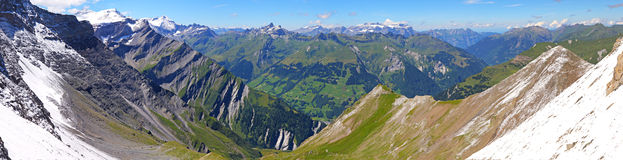 Mountain panorama from Segnas pass,. Mountain panorama in summer of the view from Segnas pass  in Switzerland with mountain ranges snow and grass Royalty Free Stock Image