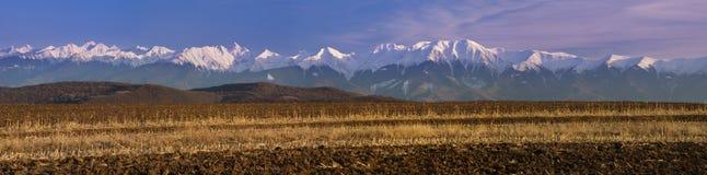 Mountain panorama snow peaks plowed field. Panorama mountain range snow peaks plowed cultivated field in spring Fagaras Transylvanian Alps Romania Stock Photos
