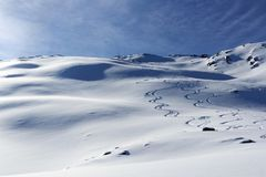 Mountain panorama with snow, ski tracks and summit cross in winter in Stubai Alps Royalty Free Stock Photography