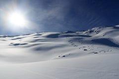 Mountain panorama with snow, ski tracks, sun and summit cross in winter in Stubai Alps Stock Photography