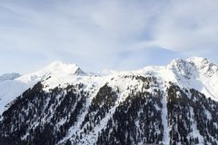 Mountain panorama with snow, trees and blue sky in winter in Stubai Alps. Austria Royalty Free Stock Images
