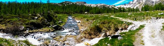 Mountain panorama with torrent full of water in summer Alpe Deve. Ro, Piedmont Italy Stock Image