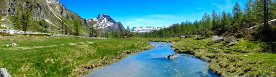 Mountain panorama with torrent full of water in summer Alpe Deve. Ro, Piedmont Italy Stock Photos