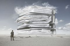 A mountain of paperwork. A man in a suit is walking towards a mountain of paperwork, daily grind concept stock photography