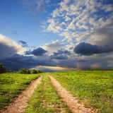 Mountain path leads through plain with green grass under blue cl. Mountain road leads through plain with green grass under blue cloudy sky and trees at the Stock Photos