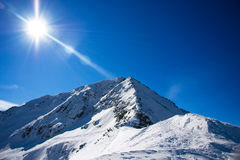 Mountain peak. The sun is shining bright against the blue sky and snowy rock royalty free stock images
