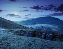 Mountain peak behind hillside with boulders at night Stock Image