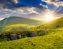 Mountain peak behind hillside with boulders at sunset. View on high mountain peak from hillside covered with white boulders and conifer trees among green grass Stock Photo