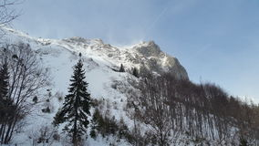 Mountain peak with blizzard upon. A sunny mountain peak in winter swiped by blizzard Stock Photo