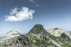 Mountain peak and a cloud on beautiful clear summer sky. In Retezat Mountains, Romania Stock Photo