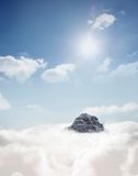 Mountain peak through the clouds Stock Images