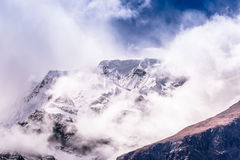 Mountain peak between the clouds. Snowy mountain peak in Nepal, Annapurna circuit Stock Photo