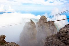 Mountain peak in the clouds with a suspension bridge. stairway to Heaven royalty free stock photos