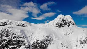 Mountain peak covered in snow on a cold winters day with blue skies and puffy clouds. Mount Bitihorn in winters time.