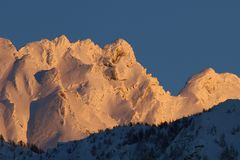 Mountain peak covered in snow in the winter. Sunrise over a mountain peak covered in snow in the winter after a storm Royalty Free Stock Images