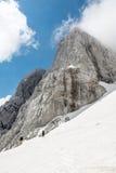 Mountain peak with descending skiiers. Jalovec, Slovenia Royalty Free Stock Photos