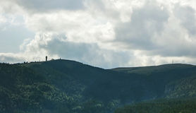 Mountain peak Feldberg with tower - distant view. Black forest trees surrounded Royalty Free Stock Image