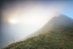 Mountain peak in fog at sunrise Stock Images