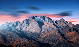 Mountain peak lighted by moonlight in autumn at night. In Dolomites, Italy. Beautiful landscape with mountains, forest on hills, blue sky with pink clouds royalty free stock photography