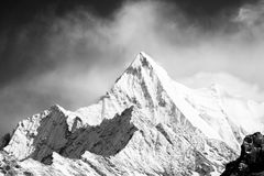 Mountain peak in monotone. With snow cover, there is clouds in background Stock Photo