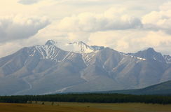 Mountain peak Munch-Sardyk - 3491 meters above sea level. `Forever white trout` in July from the side of Mongolia is the highest mountain in the Eastern Sayan Stock Images