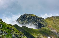 Mountain peak over the cliff and clouds. Beautiful summer scenery of Fagaras mountains Royalty Free Stock Images