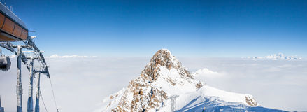 Mountain peak over the clouds in French Alps. Mountain peak seen over the clouds at the Meribel Skiing Resort in French Alps Stock Images