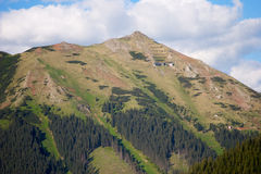 Mountain peak with radio tower. Mountain peak in Austria with radio tower on top. Just under the top, the avalanche barriers are visible with a mountain hut just Stock Photos