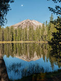 Mountain peak reflected in lake with moon Stock Image