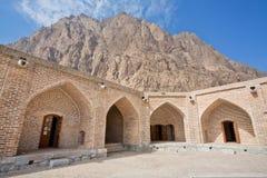 Mountain peak rises above the old building of the caravanserai Stock Image