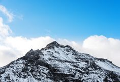 Mountain peak with snow and blue sky with white clouds in winter, winter landscape in Iceland Stock Photos