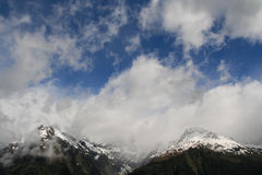 Mountain Peaks. High Mountain snow covered peaks rising majestically into the clouds Stock Photography