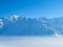 Mountain peaks above the clouds. Snow covered mountains rise above morning mist on sunny day. Shot in Chamonix valley French alps Stock Image