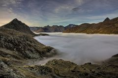 Mountain peaks above the clouds.One of the volcanoes of Kamchatka. Volcanoes of Kamchatka are fascinating. Their mysteriousness attracts many tourists from all stock images