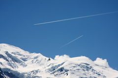 Mountain peaks with aeroplanes. Aeroplanes travelling in opposite directions over the snow capped mountains of the Mont Blanc range Royalty Free Stock Photography