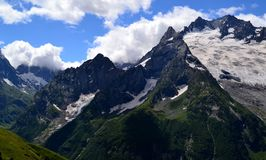 Mountain peaks against a background of white clouds. Dombay, - Karachay-Cherkessia in the basin of the Teberda in the North Caucasus Russia. Photo taken on Royalty Free Stock Photo