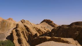 Mountain peaks of Atlas Mountains in Sahara desert in Oasis Chebika, Tunisia. Mountain landscape in national reserve park on blue sky background stock footage