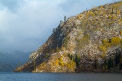 Mountain peaks with autumn forest and lake. Snowy mountain peaks with autumn forest and lake Stock Image