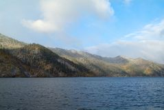 Mountain peaks with autumn forest and lake. Snowy mountain peaks with autumn forest and lake Royalty Free Stock Image