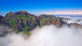 Mountain peaks in the clouds against blue orange sky. Madeira island. Mountain peaks in the clouds against blue orange sky. View from Pico do Arieiro on stock photography