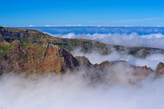 Mountain peaks in the clouds against clear blue sky. Portuguese island of Madeira. Mountain peaks in the clouds against clear blue sky. View from Pico do Arieiro royalty free stock image