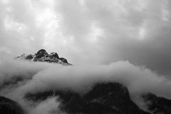 Mountain peaks in the clouds. White clouds envelop the tops of the mountains. Rocky peaks discernible through the clouds Royalty Free Stock Images
